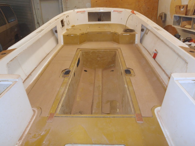 I trimmed and set the 3/4 marine plywood floor pieces in place around the coffin. This is just a temporary set up. The coffin will be removed and get cleats all around the outer edge as will the floor. The coffin will then be foamed into exact position. We will then run the drain tubes for the front compartments and rigging conduits, gas tank fill and vent, foam all open voids under the floor, install gas tank and foam into place, install the floor boards and tank deck and finally fiberglass the entire top deck.