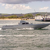 A fast luxury cruiser passes sandbanks on its way into poole harbour