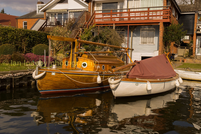 Sailing boats tied up in a riverside private mooring