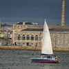 Sailing boat sails up the Tamar passed Royal William yd