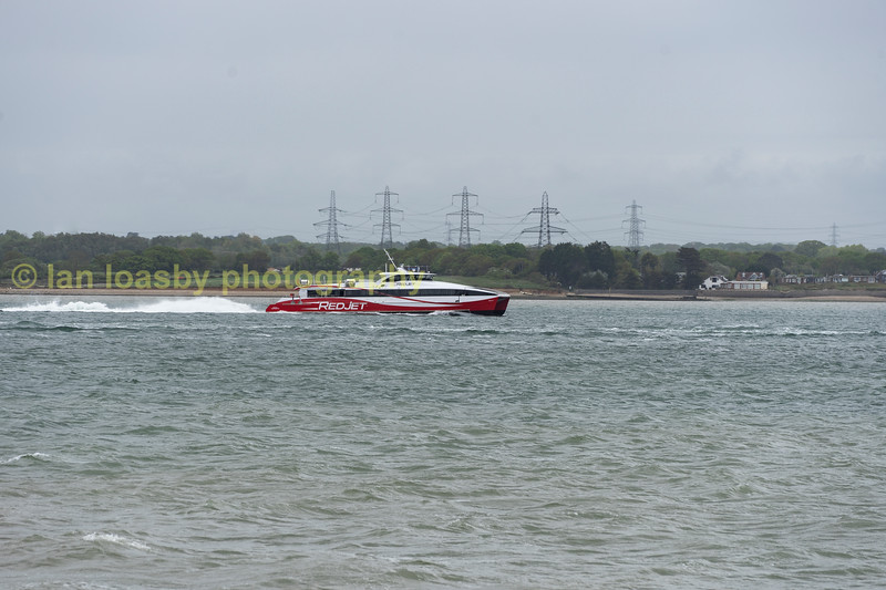 Red jet fast ferry from Southampton to The isle of Wright passing Calshot