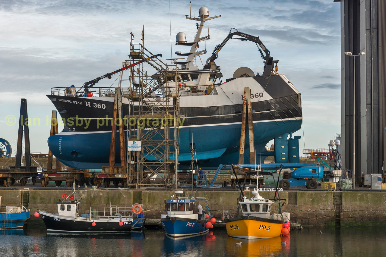 A fishing vessel out of the water under going maintenance