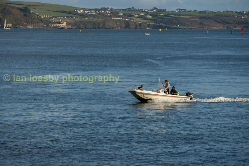 Small boat with some fishermen heading back up the Tamar riverl