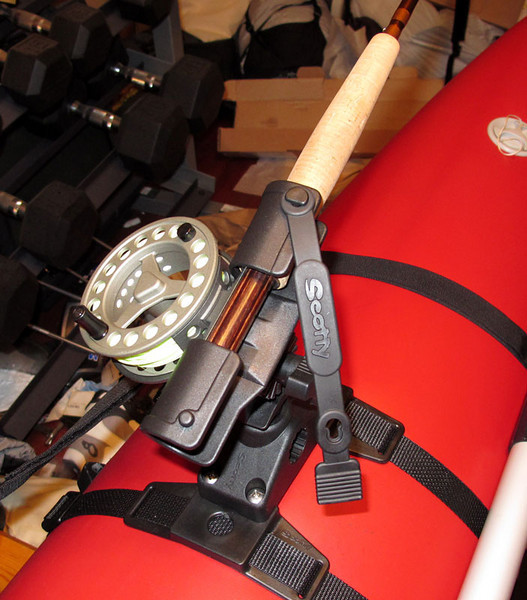 In this view, the rod and reel are inserted and the strap is open.  It would be pretty difficult for the rod to get out of that holder any way but in your hand.