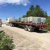 Truck trailer backs down hill to ramp to board barge Niska I.