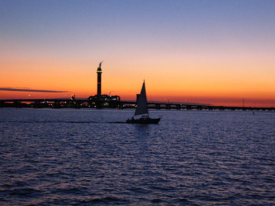 A sailboat heads for home as the sun sets over the Garden State Parkway and the local power station near Somers Point, NJ