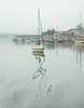 sailboat with reflections of hull and mast in waters of Boothbay Harbor Maine