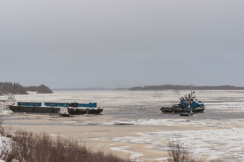 Tugs Harricana River and Nelson River on the icey Moose River starting to move a barge to winter storage.