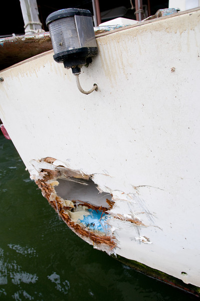 Here's the picture of the worst damage. This was a bit hard to snap, since the waves were large and it required holding the camera out past the transom as far as I could reach.<br /> <br /> The hole is about an 18-inch to 24-inch circle. The blue foam was a compartment that was foam-filled to do exactly what it was called on to do here-prevent collision damage from sinking the boat. The compartment on top is the propane storage compartment and is sealed off from the rest of the boat. Bottom line is that no water is getting in past these watertight compartments.