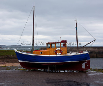 A scottish fishing boat sits on the harbour wall.