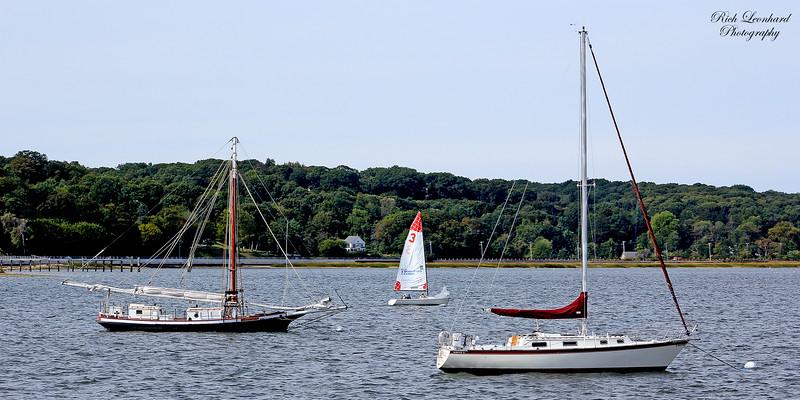 Anchored sailboats and small sailboat under sailing by.
