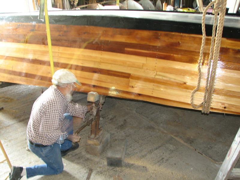 """Friday, October 2 is """"roll-over day.""""  Lynn attached five web straps to ceiling beams to make a sling.  The boat is now suspended and the """"strong-back"""" is gone.  Here he is jacking up one side of the boat to begin its roll-over."""