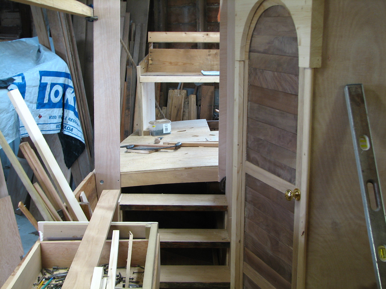 This view looks toward the aft deck with a full width sitting bench on the back.  Lynn has built three doors.  This walnut slat door will give entrance to the rear cabin, which will sleep two.