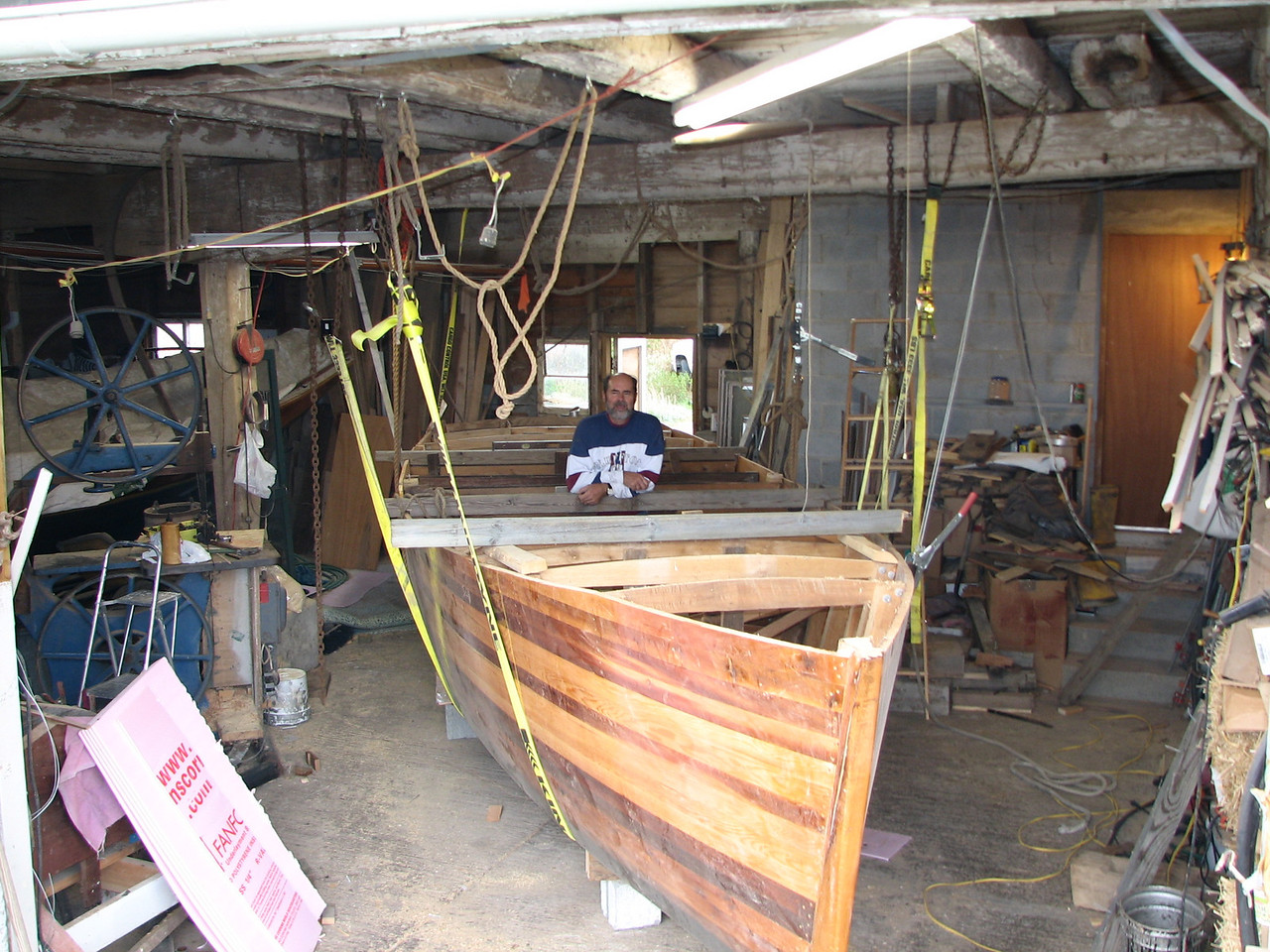 "The boat is turned and safely setting on its supports on the floor.  Don gets a feel for the view from the inside.  <br /> <br /> After due time for celebration of our creation (""And God saw that it was good."" Gen. 1:10,12,18,21,25, and 31), the work on the inside can begin."