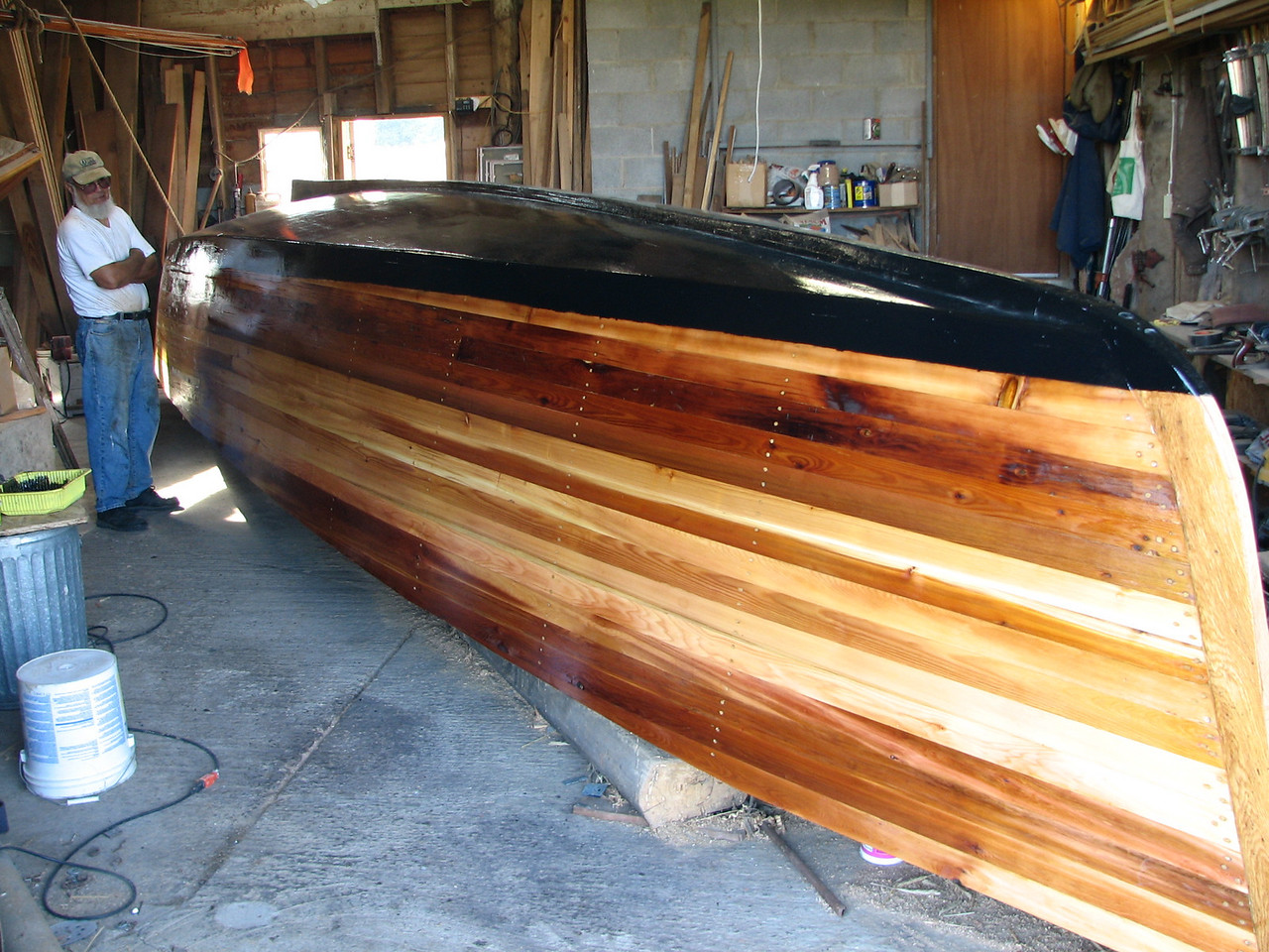 Lynn's self-reflection can be seen in the bright work of this thirty foot long boat.  The black marks the estimated water line on this hull.  We may need to paint it more accurately after we finish the boat and check it for the actual water line.