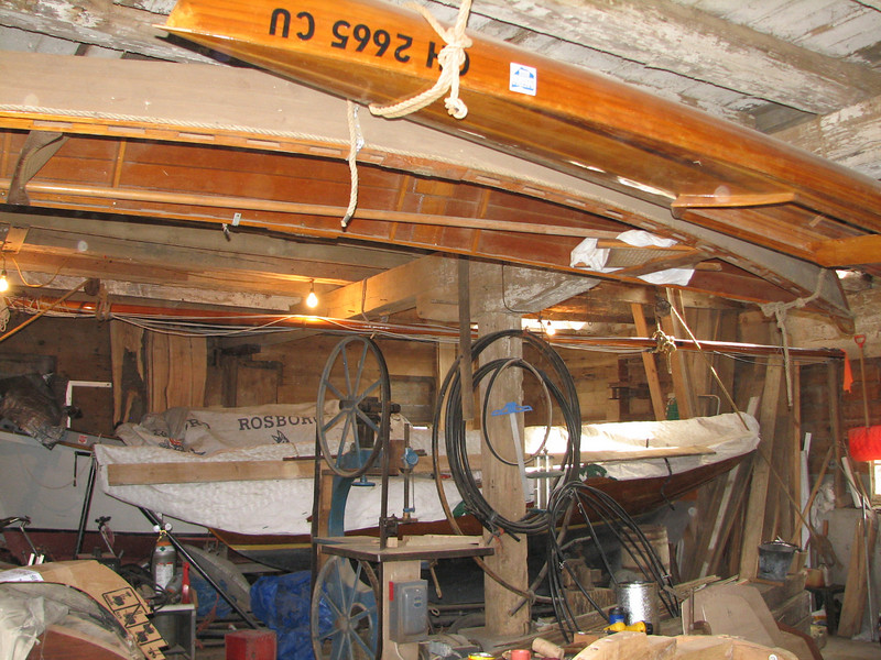 """The inside of Lynn's boat barn.  His homemade wooden boats include a cedar strip kayak, a sailing pram, a Buzzard Bay 14, and a Skipjack (plus lots of other handy """"stuff"""").  His """"lofting floor"""" is upstairs."""