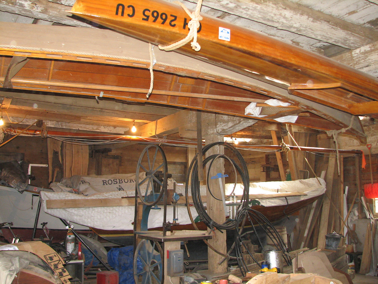 "The inside of Lynn's boat barn.  His homemade wooden boats include a cedar strip kayak, a sailing pram, a Buzzard Bay 14, and a Skipjack (plus lots of other handy ""stuff"").  His ""lofting floor"" is upstairs."