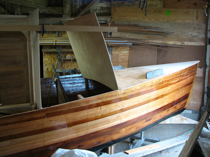 Work is now resuming after the long winter.  The front and aft decks are now installed.  The horizontal plank clamped in place helps us visualize a roofline.