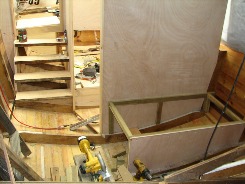 The stairway comes down from the aft deck, past the door to the aft cabin, and into the salon.  The framing is constructed for the bench with storage inside.  Masking tape on the floor shows where cabinetry will be built onto the starboard side of the boat.