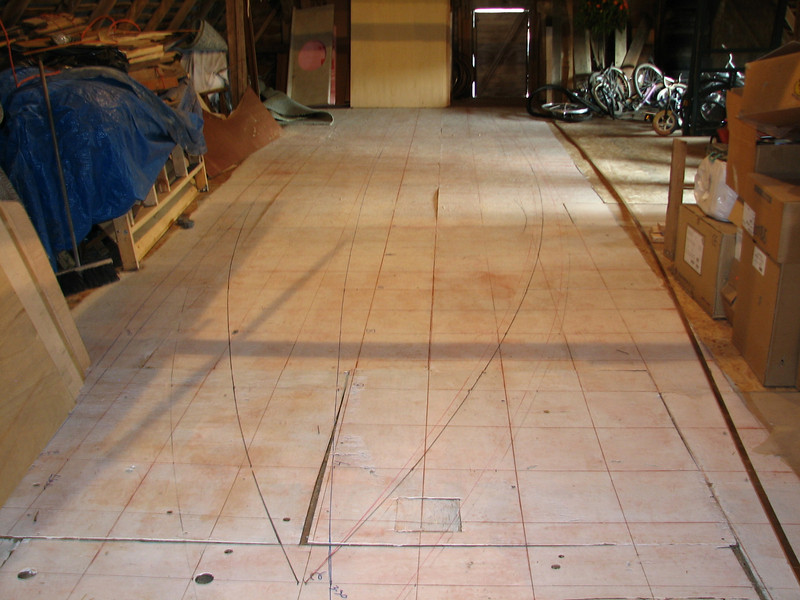 """The lofting floor shows the one foot square grid for marking out the dimensions of the hull.  We decided to make the boat thirty feet long, three feet shorter than the plans call for, and 7' 10"""" at the beam.  The intent is that it will fit into a standard 8' wide shipping container.  From this grid, the measurements for the frame patterns are determined."""
