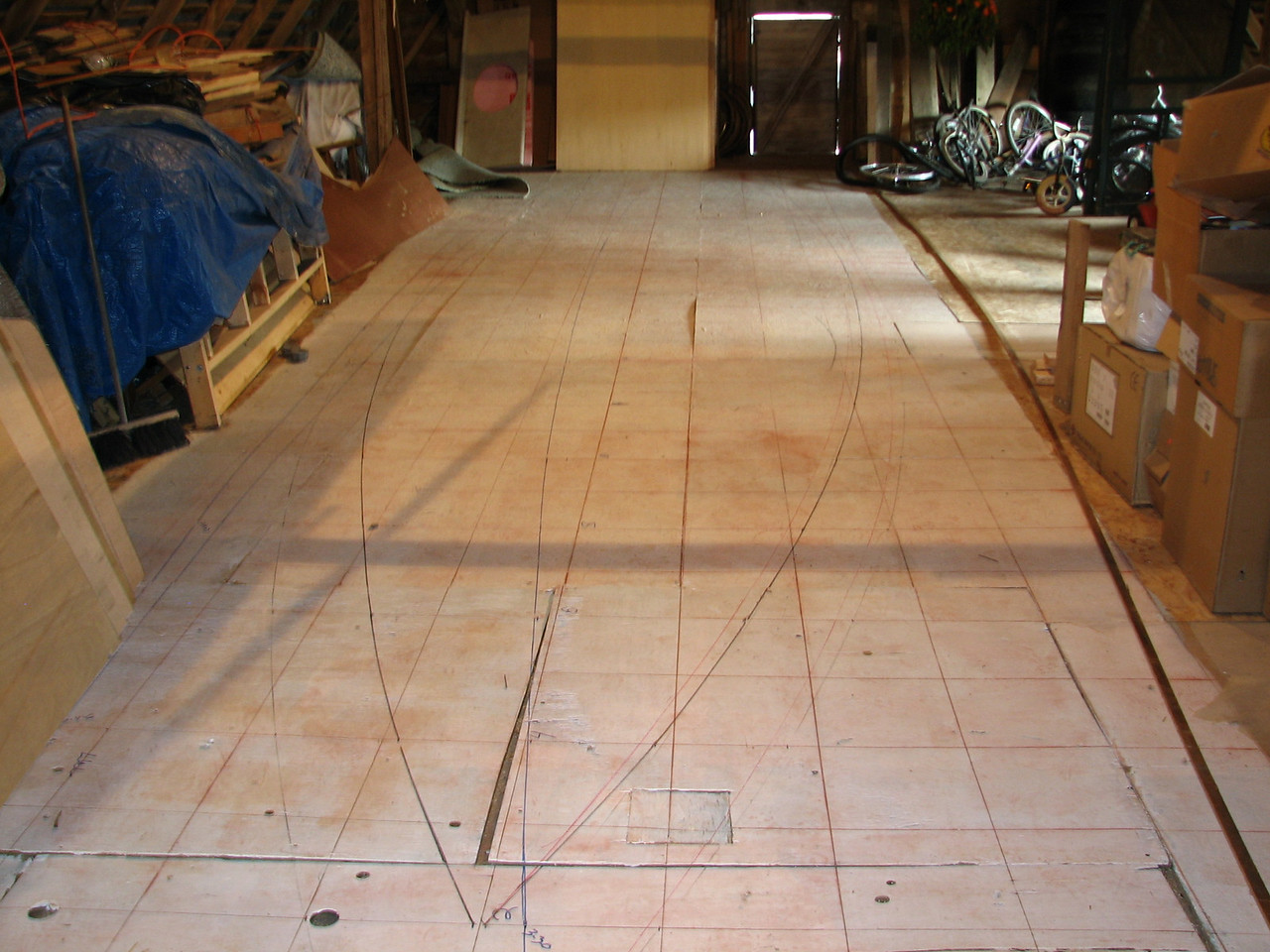 "The lofting floor shows the one foot square grid for marking out the dimensions of the hull.  We decided to make the boat thirty feet long, three feet shorter than the plans call for, and 7' 10"" at the beam.  The intent is that it will fit into a standard 8' wide shipping container.  From this grid, the measurements for the frame patterns are determined."