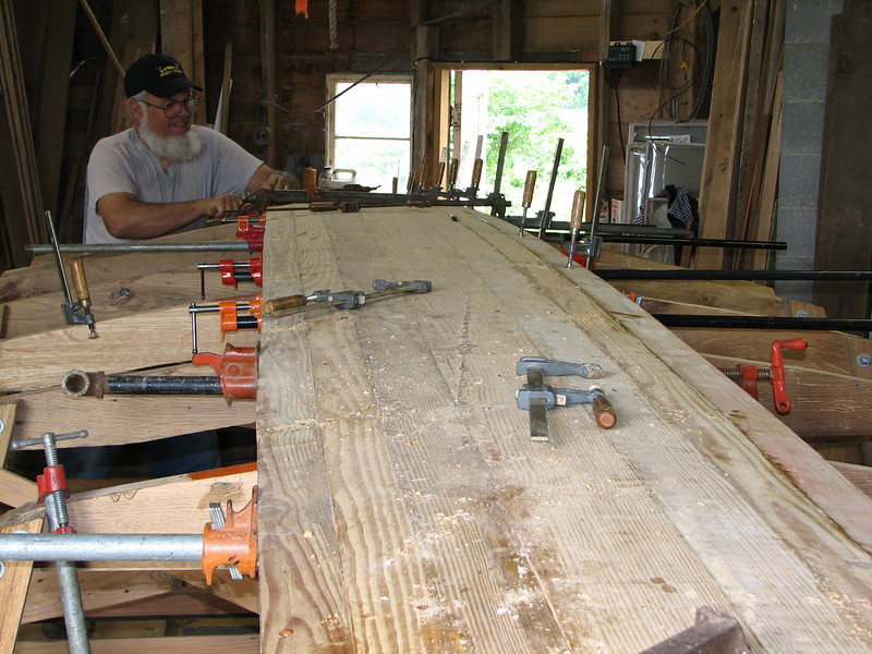 The planking is progressing well.  Resin is mixed with wood flour, or very fine sawdust, until it takes on the consistency of an oily peanutbutter.  It is applied to the edge of the plank with enough thickness that it squeezes out when the bar clamps apply pressure.