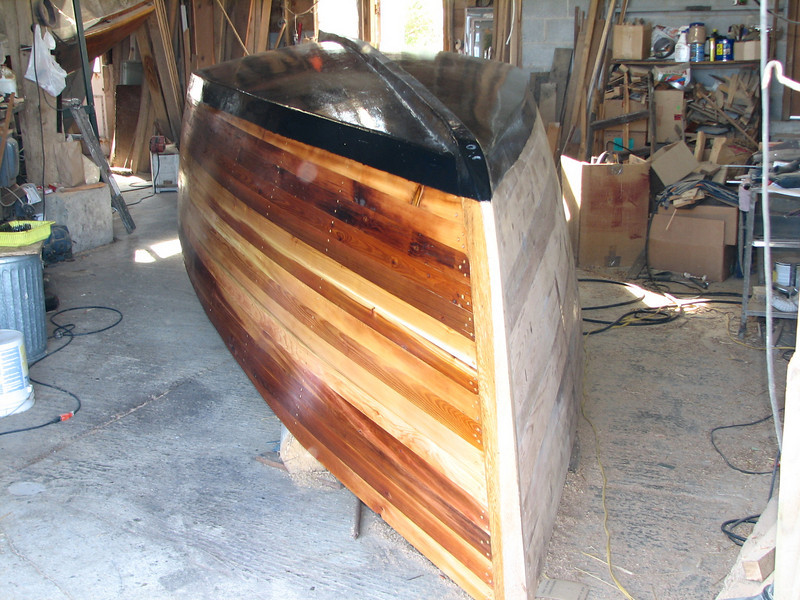 """The left side of the picture has two coats of resin on it, and the right side is still unfinished.  The resin really brings out the colors in the natural wood.  Highly finished natural wood is called """"bright work.""""<br /> <br /> The black botton is graphite paint which is supposed to decrease the friction of the water on the hull."""