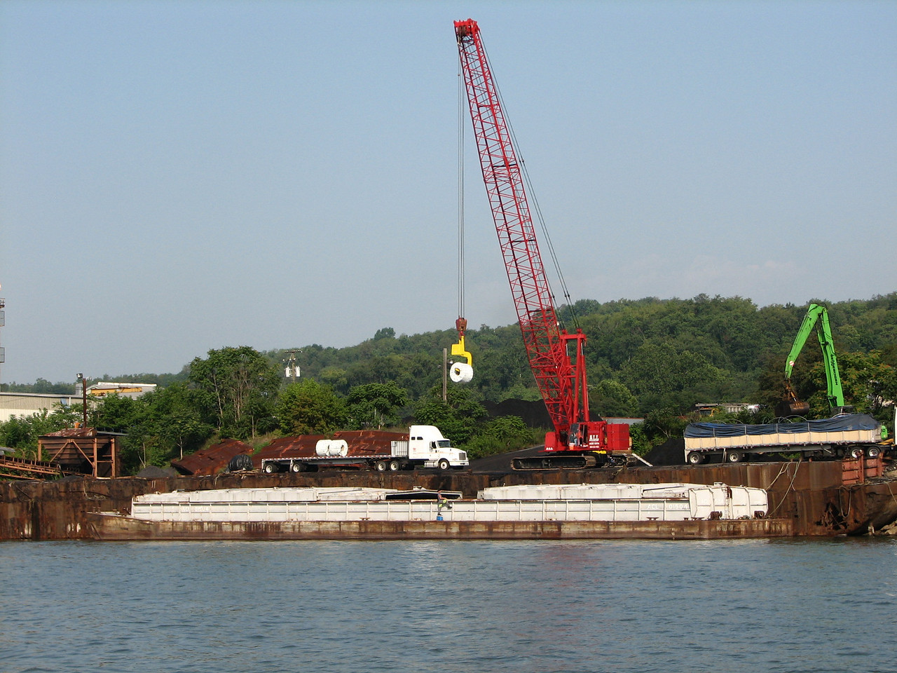 A heavy duty crane loading rolled steel from the barge onto a semi flatbed.