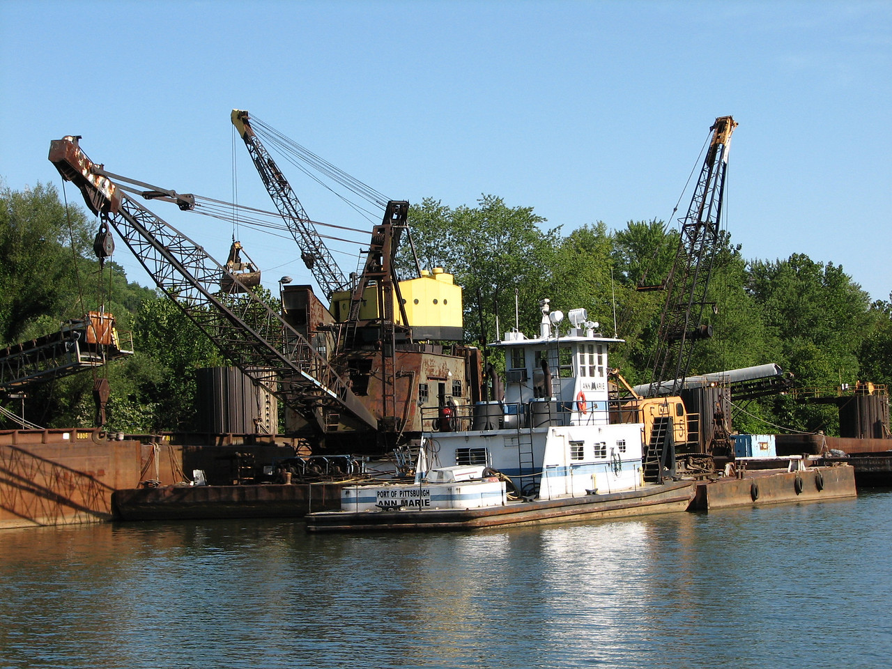 Multiple cranes include clam shell cranes for unloading coal, sand, etc. from barges onto trucks or hoppers.