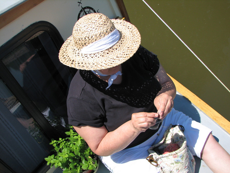 Elaine knits on the fore-deck with a token potted plant by her side.