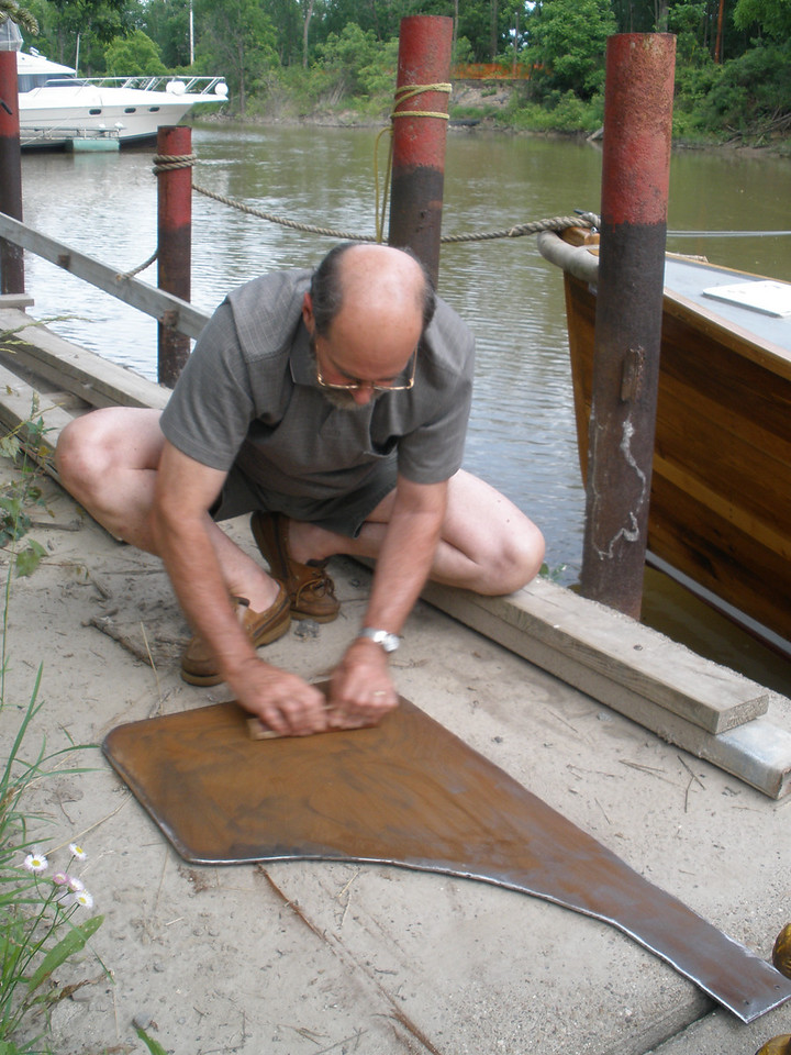 sanding the rust off the metal rudder.