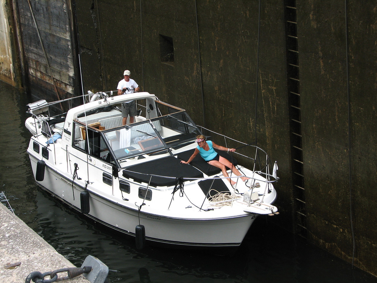 A power boat locking through lock 42.  Persons both fore and aft hold on to the cable to secure the position of their boat as the water gushes into the lock  chamber.
