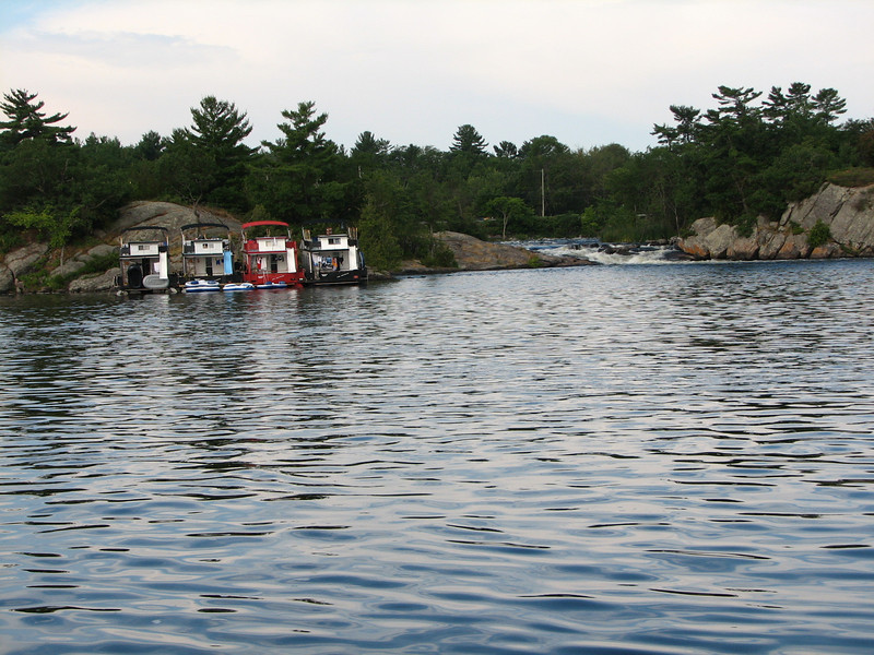 The party of four large houseboats anchor overnight at the rapids.