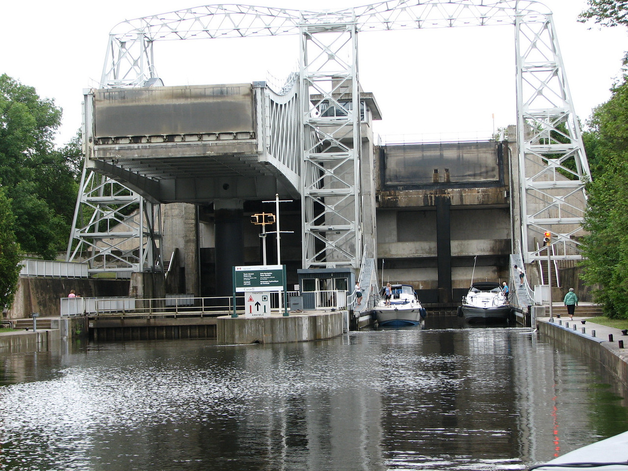 We await for the boats or leave so we can enter.  The end gate of the lower container is lowering to give the boats the proper depth for them to exit safely.  Another gate can be seen fifteen meters above the boats, holding back the water from the upper level of the canal.