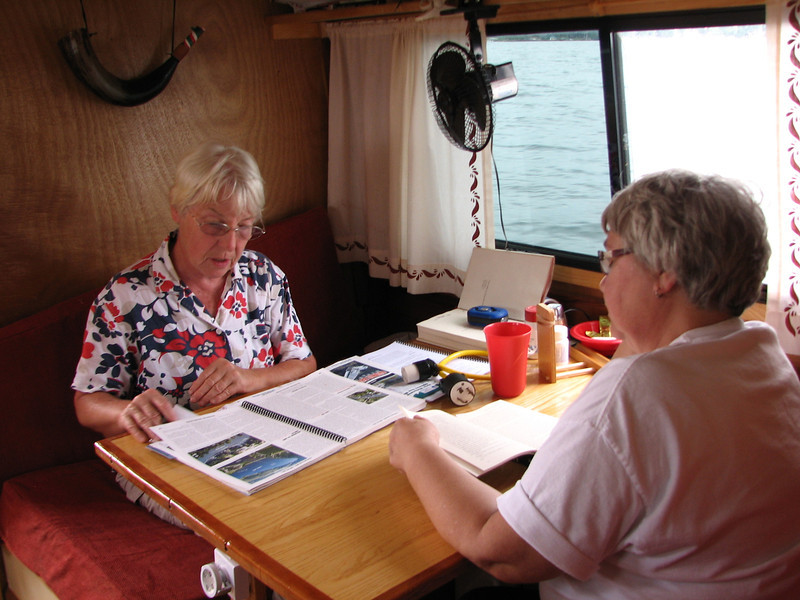 "Elaine and Linda kill time and try to calm their nerves as we cross Lake Simcoe. This is the largest body of water we encountered on this trip.  At the south end of Lake Couchiching is the Atherley Narrows, just east of Orilia.  We had a huge stern wheel type cruise boat follow us through the narrows and under highway 12, and Lynn called the captain on the boat to explain we were going as fast as we could.  He then headed south west (likely to Barrie) as we headed southeast. <br /> <br /> The trek across Lake Simcoe to the next stretch of the canal is about twenty km of open water.  For the most part, the sky was blue and the winds were moderate, but a menacing cloud front could be seen off to the west.  At one point when I was taking my turn at the wheel and the other three were below, I noticed a very unique ""rogue wave"" rolling toward us from our starboard side.  It was a single long white wave that seemed to stretch for miles, and appeared to be about three feet high.  It was not created by any passing boats because we had not seen a boat in the last half hour.  We were all alone.  I called Lynn to come up to see it just before we hit it.  I steered into it so we could take it by our length rather than be broad-sided.  As it passed on, the lake was again calm."