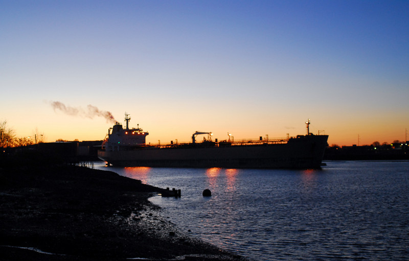 The Irving Tanker New England shifts from one oil terminal to another in Chelsea Creek at twilight.