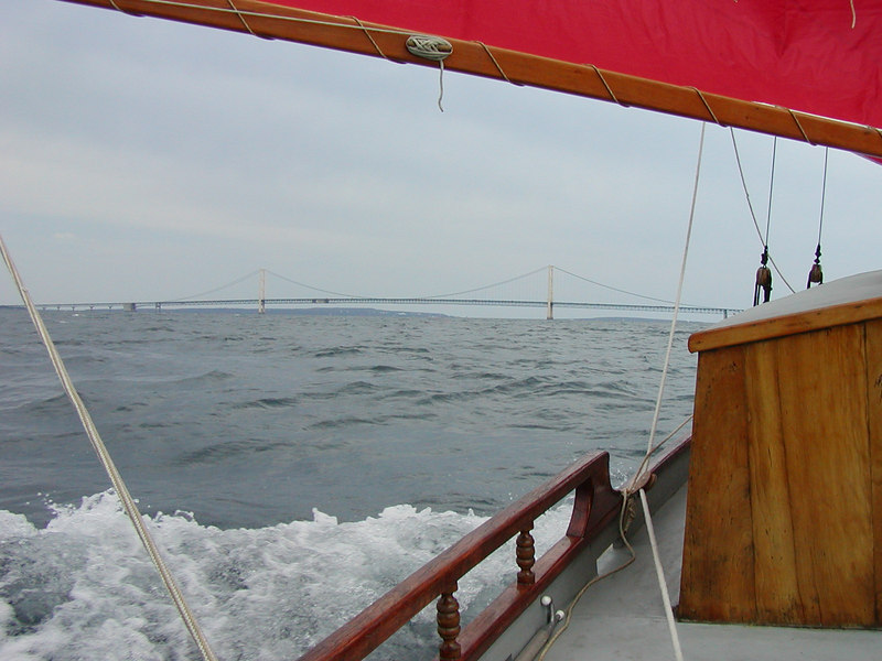 The Linda Jean rushes forward under full sail with the Mackinaw bridge in the distance. This bridge spans the five miles between the upper and lower peninsulas of Michigan.