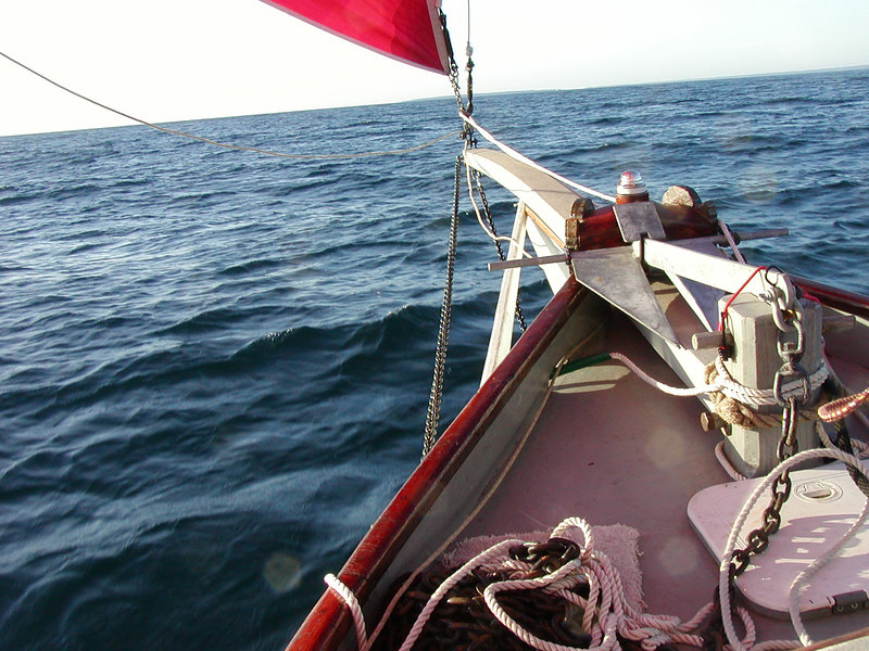 "This twenty-five foot boat has a bowsprit that adds another six feet to the overall length.  The bowsprit secures the foresail in a proper position to chanel the wind outside the mainsail.  This provides the forward ""lift"" affect, much like an airplane wing.<br /> <br /> The foredeck provides a space for the various lines including anchor chain and line, and jib downhaul line. A hatch gives access to the sail storage below deck and airflow for ventilation to the cabin.  The haulyards (the lines that raise and lower the sails) are also accessable here and are tied off at the mast."
