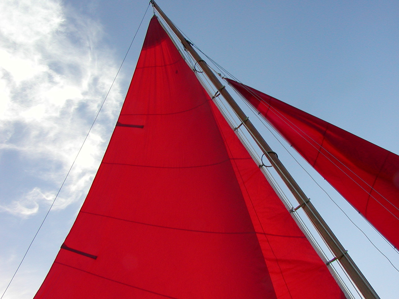Lynn, with the help of wife, Linda, sewed his own sails.  Why red?  It was on sale, of course. The mainsail is tied to wooden hoops that slide easily up and down the wooden mast, a technique common on older wooden boats.