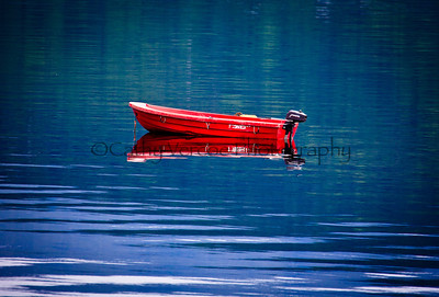 A lone dinghy sits on a placid loch in Scotland