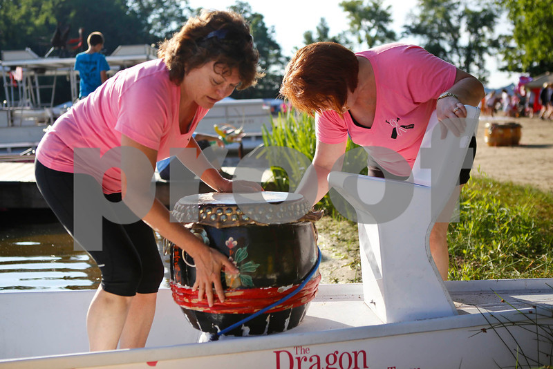 "Akron resident Pam Massoli (left) and Copley resident Connie Delehanty  mount a drum on a dragon boat at the Portage Lakes Dragon boat festival a the Portage Lakes State Park in New Franklin, Ohio on July 13 2013.  The activities started down an the beach with a ceremonial eye-dotting ""awakening of the dragons and  three dragon boat teams headed to the finish line every few minutes.  Lew Stamp Photography."