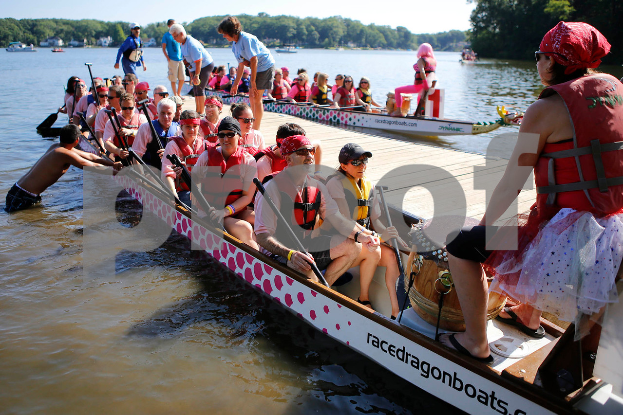 """Teams return to dock after a race at the Portage Lakes Dragon boat festival a the Portage Lakes State Park in New Franklin, Ohio on July 13 2013.  The activities started down an the beach with a ceremonial eye-dotting """"awakening of the dragons and  three dragon boat teams headed to the finish line every few minutes.  Lew Stamp Photography."""