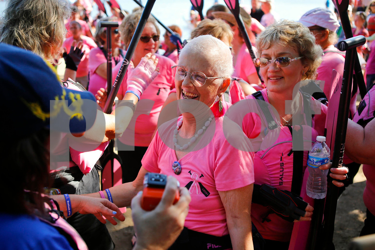 "Massillon resident and Catholic Sister, Susie Corrigan (center) celebrates with teammates after race at the Portage Lakes Dragon boat festival a the Portage Lakes State Park in New Franklin, Ohio on July 13 2013.  The activities started down an the beach with a ceremonial eye-dotting ""awakening of the dragons and  three dragon boat teams headed to the finish line every few minutes.  Lew Stamp Photography."