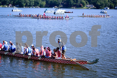 "Dragon boats race down the course in back ground as the next boats for the next heat leave the dock in foreground, at the Portage Lakes Dragon boat festival a the Portage Lakes State Park in New Franklin, Ohio on July 13 2013.  The activities started down an the beach with a ceremonial eye-dotting ""awakening of the dragons and  three dragon boat teams headed to the finish line every few minutes.  Lew Stamp Photography."