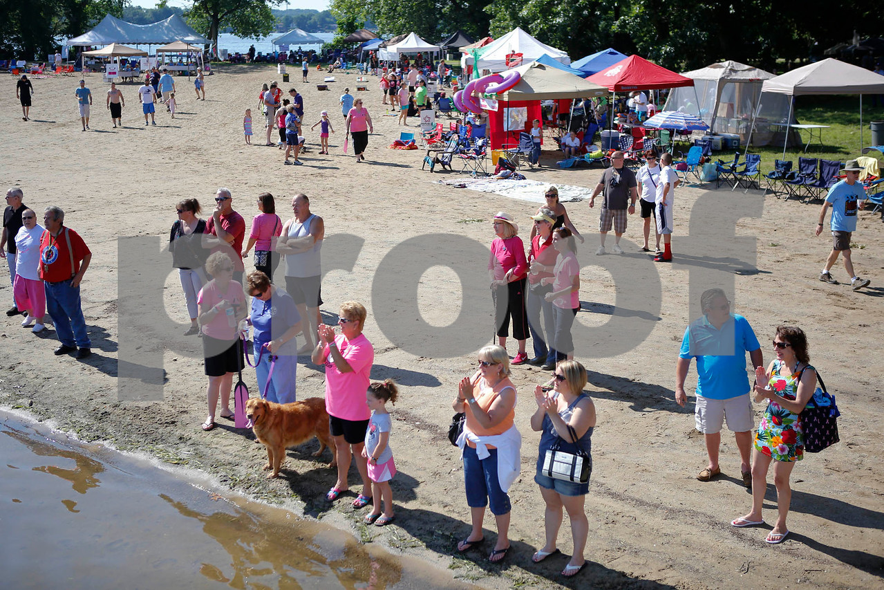 """Race fans cheer a race from the beach at the Portage Lakes Dragon boat festival a the Portage Lakes State Park in New Franklin, Ohio on July 13 2013.  The activities started down an the beach with a ceremonial eye-dotting """"awakening of the dragons and  three dragon boat teams headed to the finish line every few minutes.  Lew Stamp Photography."""