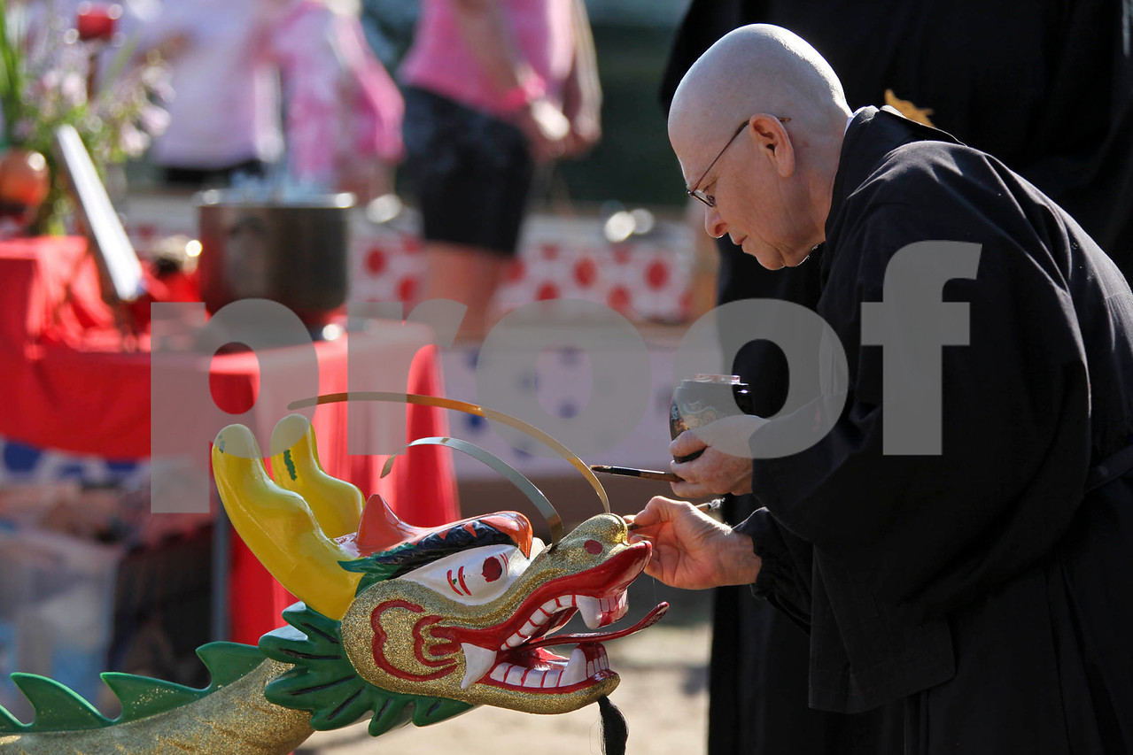 """Buddist monk Myoshu Wren be gins the """"awakening"""" ceremony by dotting the dragon's eyes at the Portage Lakes Dragon boat festival a the Portage Lakes State Park in New Franklin, Ohio on July 13 2013.  The activities started down an the beach with a ceremonial eye-dotting """"awakening of the dragons and  three dragon boat teams headed to the finish line every few minutes.  Lew Stamp Photography."""