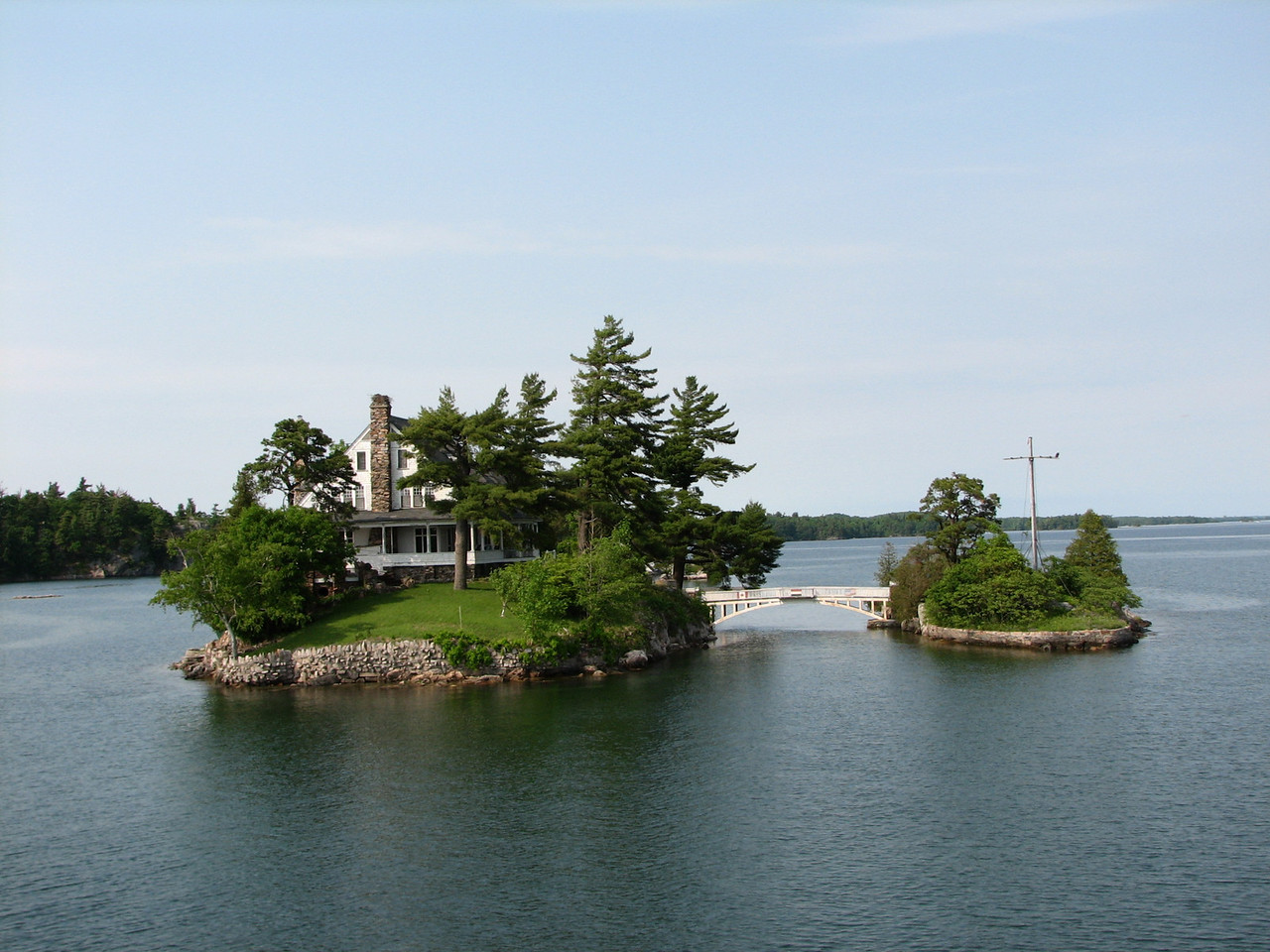Two of the 1700 islands in the area, is divided by the US-Canada border, making this the smallest international bridge. (Canada is on the left; the US is the small island.)<br /> <br /> To qualify as an island it must have at least two trees on it, otherwise it is an islet or a shoal.  It must be at least two acres in size to build a house or cabin upon it.