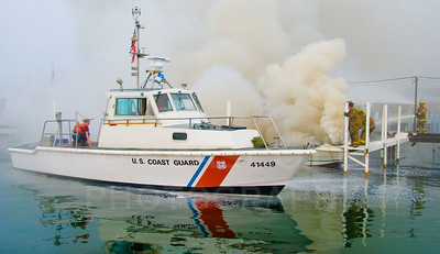 The U.S. Coast Guard assists Detroit firefighters in extinguishing a small boat fire.