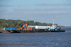 Small tug works with Tug Nelson River to move a barge in Moosonee 2018 August 17.
