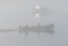 Canoe and taxi boat passing in morning fog on the Moose River.